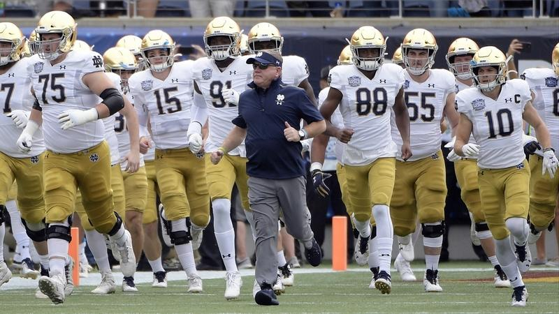 In this Dec. 28, 2019, file photo, Notre Dame head coach Brian Kelly runs onto the field with his players before the Camping World Bowl against Iowa State in Orlando, Fla. Notre Dame has agreed to play an ACC schedule for one season, but won't be able to continue its series against Navy this fall. (AP Photo/Phelan M. Ebenhack, File)