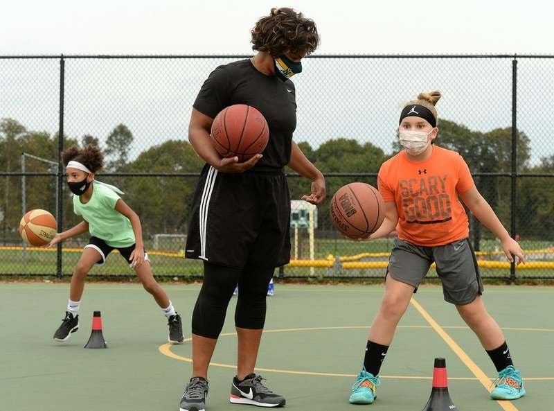 Coach Tammy Millsaps works with a player on how to pocket the ball during the New London Basketball Skillz Clinic at Toby May Park Thursday, Sept. 17, 2020, in New London.  Millsaps is the new girls´ basketball coach at New London High School. (Dana Jensen/The Day)