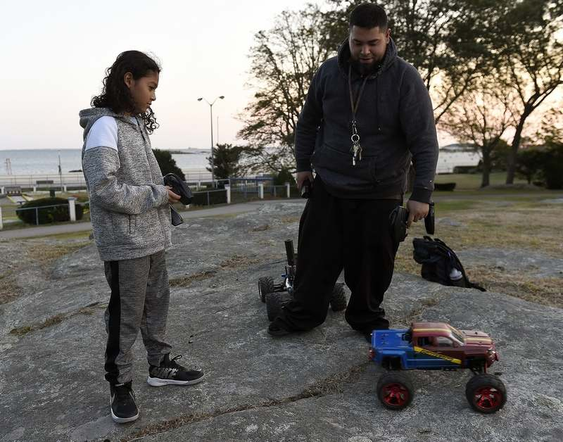 09/21/2020 :: REGION  :: STANDALONE :: Eudocio Cruz and his son Lorenzo, 12, use nitro powered remote controlled cars along the rocks at Ocean Beach Park on Monday, September 21, 2020 in New London. Eudocio says he prefers using nitro over battery because of the troubleshooting you have to do. þÄúStuff breaks, you have to fix it, sometimes thatþÄôs the most fun part,þÄù he said. (Sarah Gordon / The Day)