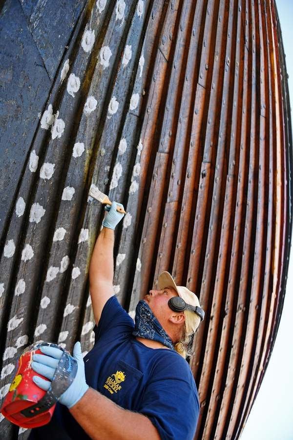 Casey Cochran, a shipwright with Mystic Seaport Museum, applies an epoxy paint to the bronze spike fasteners on the hull of the replica Viking ship Draken Harald Harfagre on Thursday, Oct. 15, 2020, at the Henry B. duPont Preservation Shipyard.  (Sean D. Elliot/The Day)