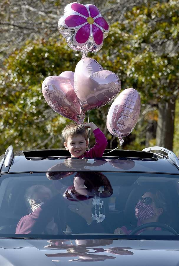 "Sterling Roshto, 4, of New London, waves from a car as mom Tanya, right, and grandmother Ramona Wujtewicz look on during a Pink Celebration and Drive Through event for breast cancer survivors at Rocky Neck State Park on Sunday, October 18, 2020. The event, hosted by Making Strides Against Breast Cancer of New London County, was planned after the COVID-19 pandemic canceled their annual walk to raise awareness and funds. Participants were encouraged to decorate their cars as they drove through the park where there was a survivor recognition tent and a tribute garden set up. ""We thought it was important to recognize another year has passed for our survivors,"