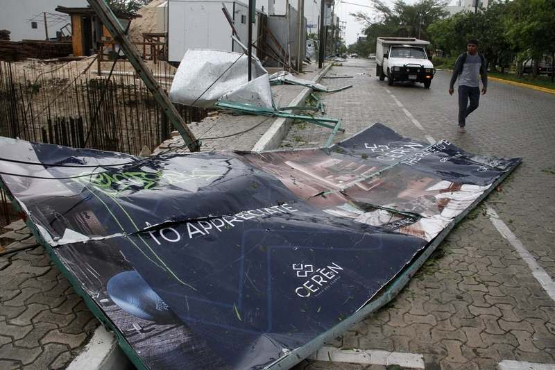 A billboard lays on the ground, toppled by Hurricane Zeta in Playa del Carmen, Mexico, early Tuesday, Oct. 27, 2020. Zeta is leaving Mexico's Yucatan Peninsula on a path that could hit New Orleans Wednesday night. (AP Photo/Tomas Stargardter)