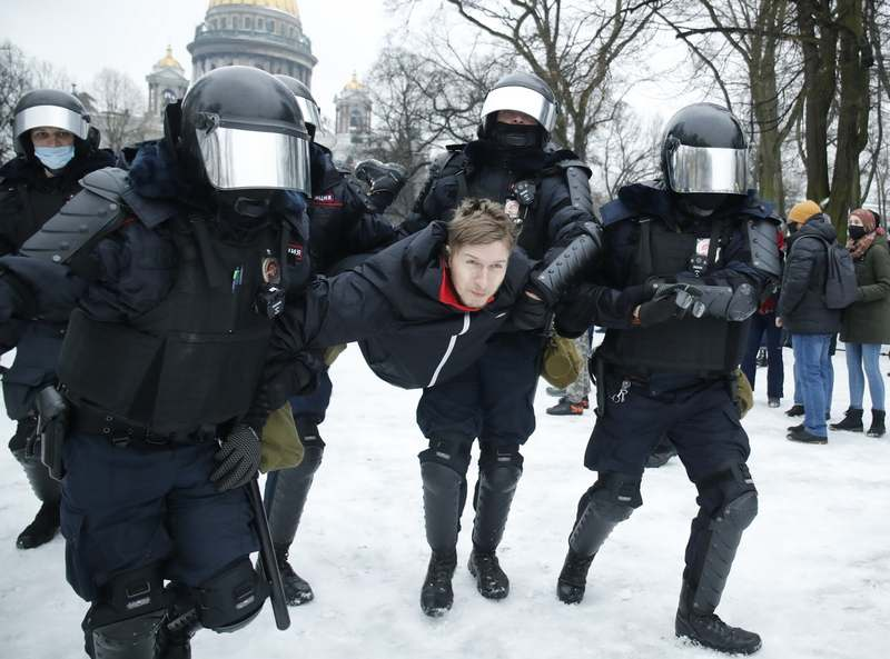 Police detain a man during a protest against the jailing of opposition leader Alexei Navalny as people gather in St. Petersburg, Russia, Saturday, Jan. 23, 2021. Russian police are arresting protesters demanding the release of Navalny at demonstrations in the country's east and larger unsanctioned rallies are expected later Saturday in Moscow and other major cities. (AP Photo/Dmitri Lovetsky)