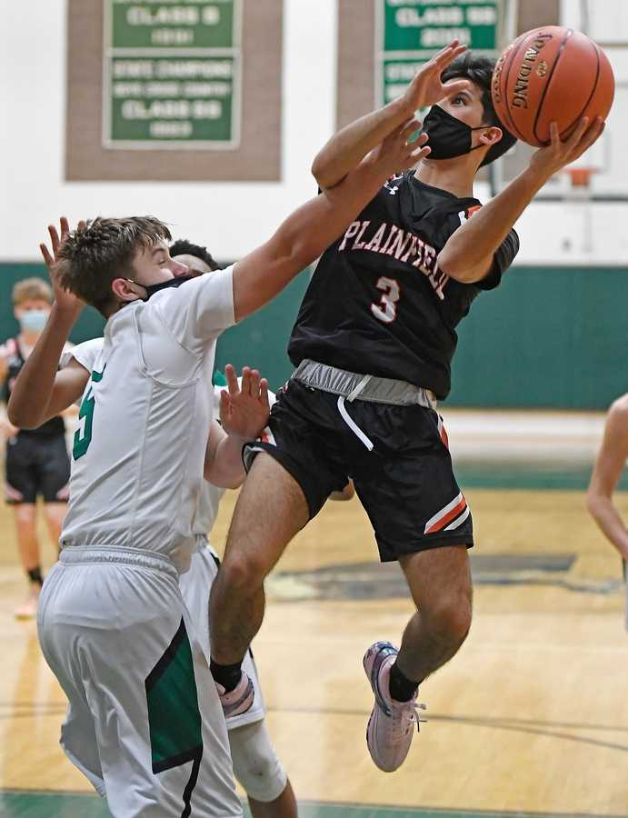 Plainfield guard Jalen Arriaga (3) puts up a shot over Griswold defender Kyle Roode in ECC north division boys basketball action Monday, February 22, 2021 in Griswold.  (Sean D. Elliot/The Day)
