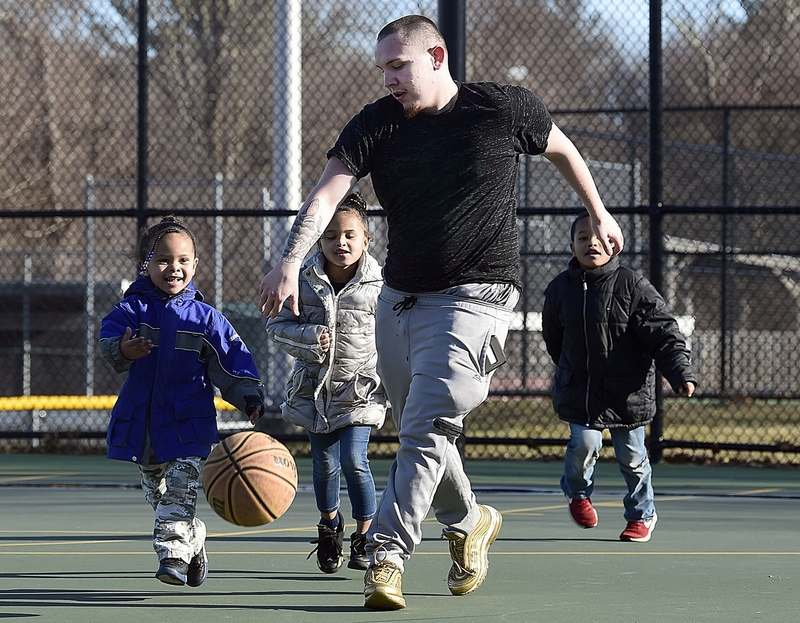 Zackerie Kirschner is chased by siblings, from left, Maciyia, 4, Malaiya, 5, and Mason Heath Jr., 5, children of his girlfriend, Whitney Heath, not pictured, as they play basketball Wednesday, Feb. 24, 2021, at Toby May Park in New London.  (Sarah Gordon/The Day)