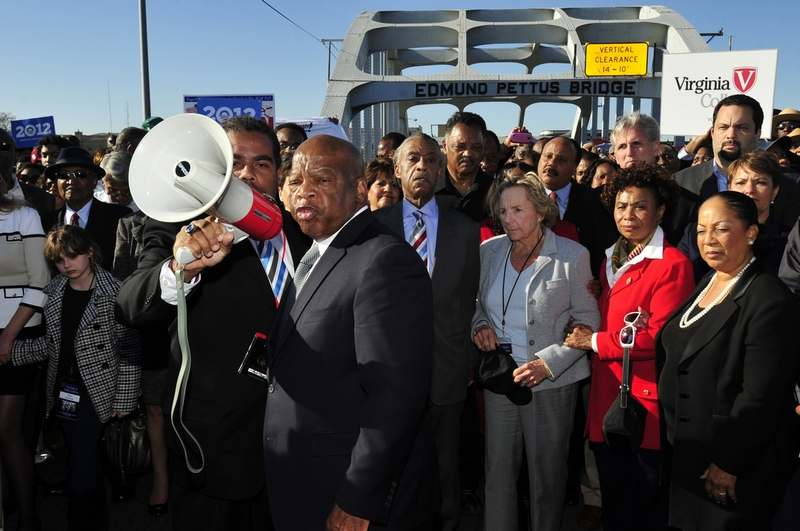 In this March 4, 2012, file photo, U.S. Rep. John Lewis, D-Ga., center, talks with those gathered on the historic Edmund Pettus Bridge during the 19th annual reenactment of the