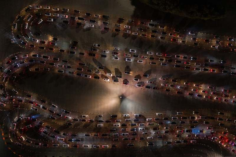 People wait in vehicles at a COVID-19 mass vaccination site at the Dodger Stadium parking lot in Los Angeles on Feb. 4, 2021. (Bloomberg photo by Bing Guan)