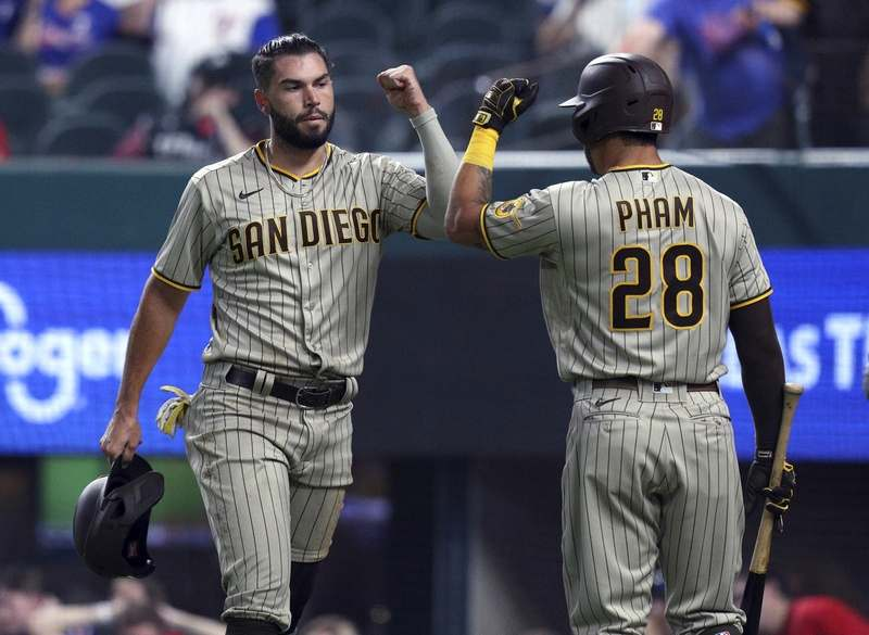 San Diego Padres Eric Hosmer (30) fist-bumps Tommy Pham (28) after scoring against the Texas Rangers during the first inning of a baseball game Friday, April 9, 2021, in Arlington, Texas. (AP Photo/Richard W. Rodriguez)