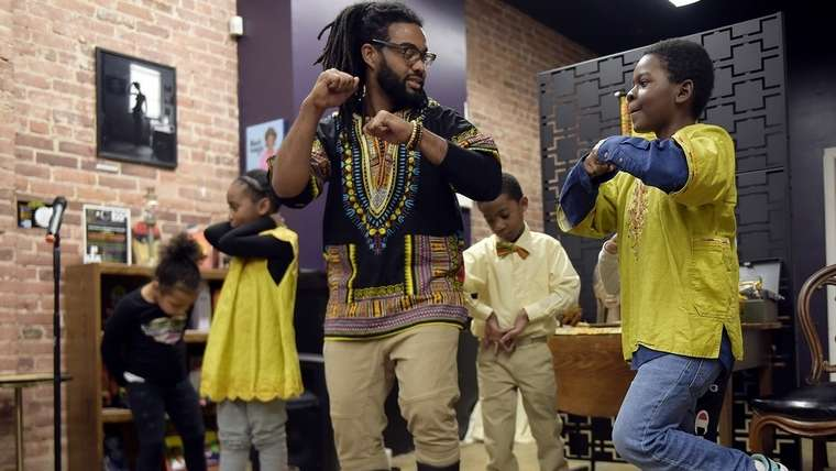 Josh Brown, center, works on teaching a step routine to Parrish Boyd, 8, of New London during a Kwanzaa Celebration at Cultured Studios in New London on Sunday, December 29, 2019. (Sarah Gordon/The Day)