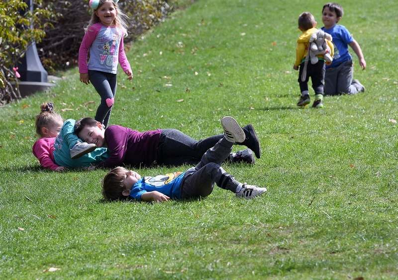Maya Muscella, center, 6, collides with her sister Maisy, 3, both of New London, as they roll down the hill Tuesday, April 13, 2021, at the Connecticut College Arboretum in New London.  (Sarah Gordon/The Day)