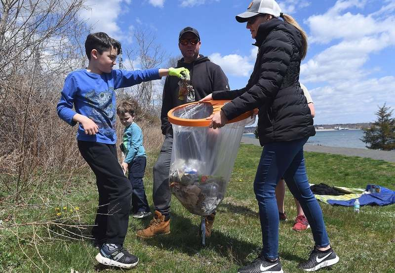 Declan McGoldrick, 8, reacts to holding a piece of trash as he puts it into a bag held by his mother Danielle, as brother Desmond, 5, and dad Sean look on, all of Waterford, as they participate in a cleanup organized by Ocean Recovery Community Alliance at Hole in the Wall Beach in Niantic on Sunday, April 18, 2021.  The nonprofit organization, which is focused on building a community to act as stewards of oceans, beaches and waterways, has more cleanups planned for the month of April across Connecticut and Rhode Island.  For details see https://ccar.us/action-center/orca/. (Sarah Gordon/The Day)
