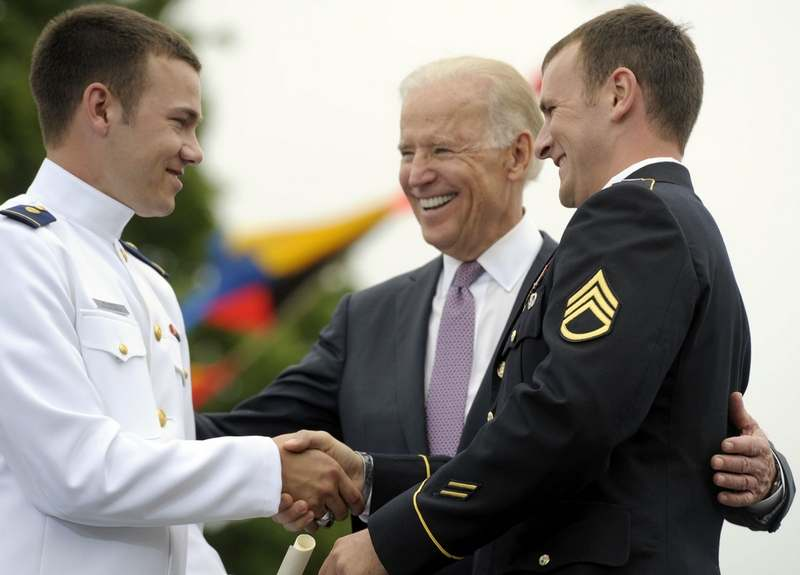 Vice President Joe Biden joins the embrace as Newly graduated United States Coast Guard ensign Kevin Wissner, left, accepts his commission from his brother, Purple Heart recipient Staff Sgt. Nicholas Wissner, US Army Reserve,  during the 132nd Commencement at the United States Coast Guard Academy Wednesday, May 22, 2013. (Sean D. Elliot/The Day)