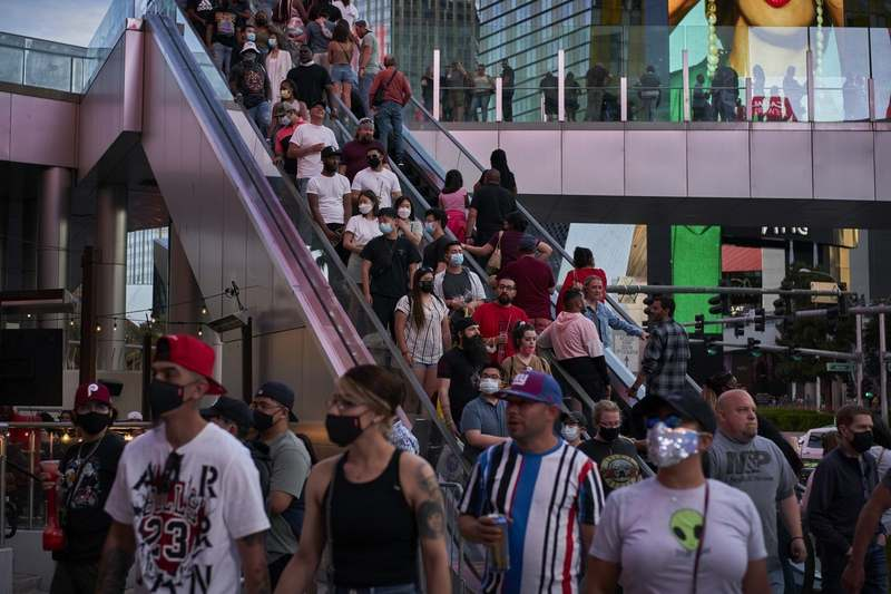People ride an escalator along the Las Vegas Strip, Saturday, April 24, 2021. Las Vegas is bustling again after casino capacity limits were raised Saturday, May 1, to 80% and person-to-person distancing dropped to 3 feet. (AP Photo/John Locher)