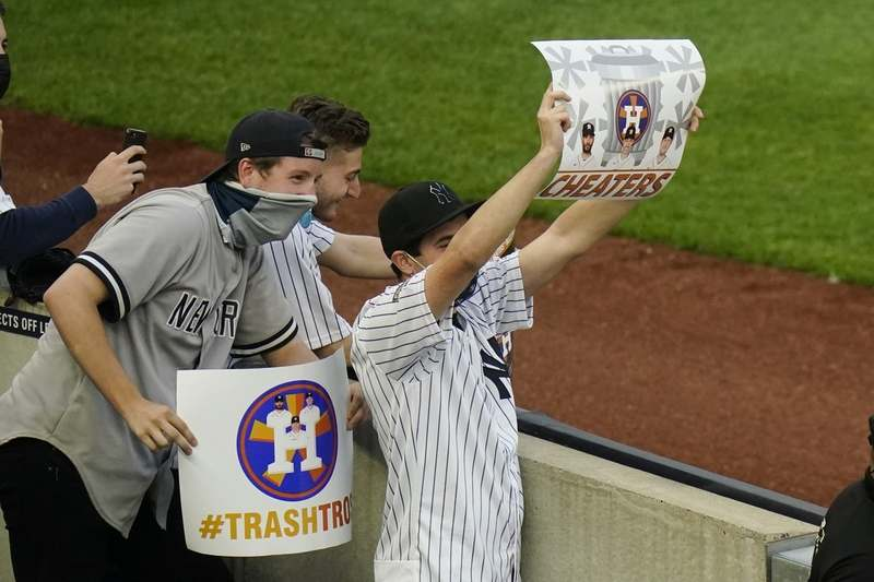 New York Yankees fans hold signs before the start of a baseball game between the New York Yankees and the Houston Astros Tuesday, May 4, 2021, in New York. (AP Photo/Frank Franklin II)