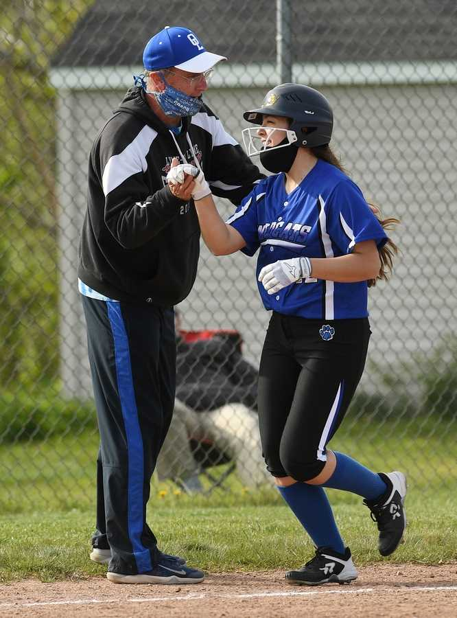 Old Lyme´s Jamie Bucior (12) and coach Tim Gavin celebrate her home run as she rounds third base during the softball game against Old Saybrook Friday, May 7, 2021, at Old Saybrook High School.  (Dana Jensen/The Day)