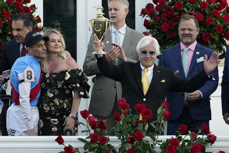 Trainer Bob Baffert holds up the winner's trophy as jockey John Velazquez, left, watches after their victory with Medina Spirit at the Kentucky Derby on May 1 in Louisville, Ky. (Jeff Roberson/AP Photo)