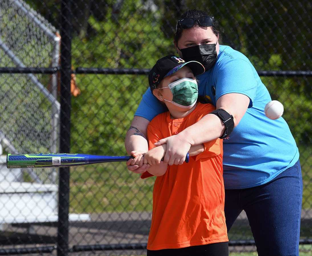 Jessica Sterns helps her daughter Gabrielle Carrico, 7, take a swing at bat Sunday, May 9, 2021, during a baseball game at the Miracle League of Southeastern Connecticut Field in East Lyme. (Sarah Gordon/The Day)