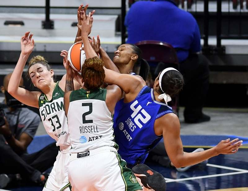 Connecticut Sun forward DeWanna Bonner, back, and center Brionna Jones (42) battle Seattle Storm forward Katie Lou Samuelson (33) and center Mercedes Russell (2) for the rebound in Sunday's WNBA game at Mohegan Sun Arena.  (Sean D. Elliot/The Day)