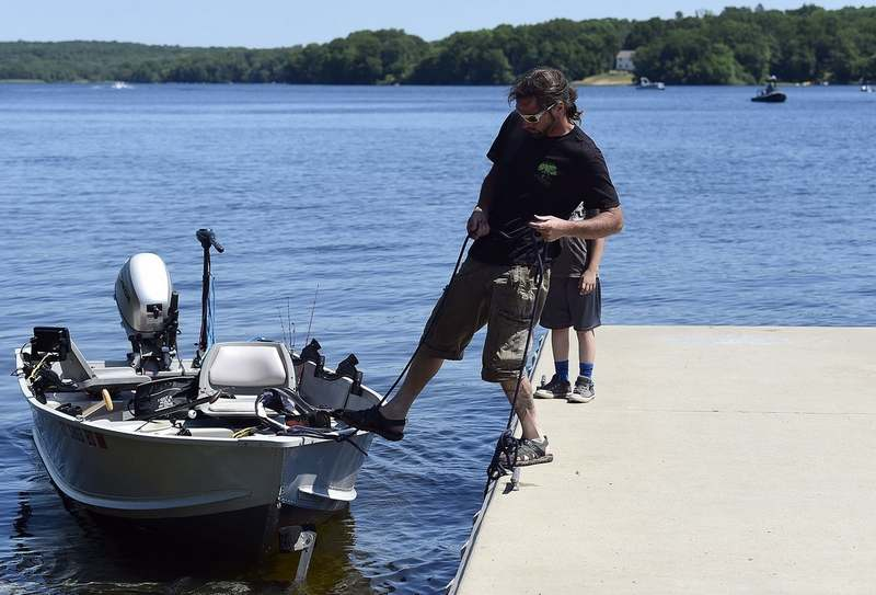 Evan Groom and his son Jacob, 10, of East Haddam, pull their boat back onto the dock after a morning of fishing at Gardner Lake State Park in Salem on Sunday, June 13, 2021. (Sarah Gordon/The Day)