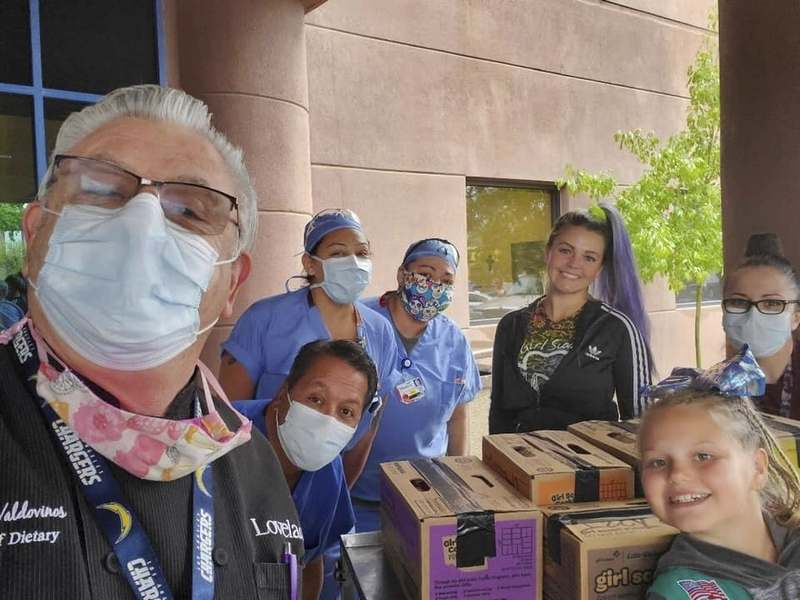 This undated photo provided by Girl Scouts of New Mexico Trails shows Henrique Valdovinos, left, and other health care workers at the Lovelace Women's Hospital in Albuquerque, New Mexico, receiving a donation of cookies as part of the Girl Scouts' Hometown Heroes program. (Girl Scouts of New Mexico Trails via AP)