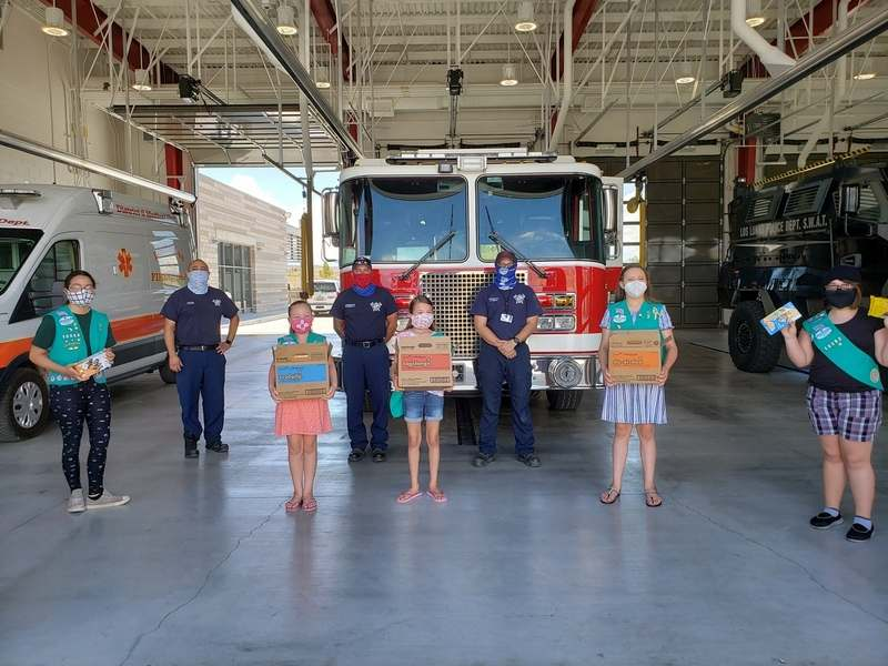 This undated photo provided by Girl Scouts of New Mexico Trails shows scouts donating cookies to firefighters in Los Lunas, New Mexico, as part of the Hometown Heroes program. As the coronavirus pandemic wore into the spring selling season, many Girl Scout troops nixed their traditional cookie booths for safety reasons. That resulted in millions of boxes of unsold cookies. (Girl Scouts of New Mexico Trails via AP)