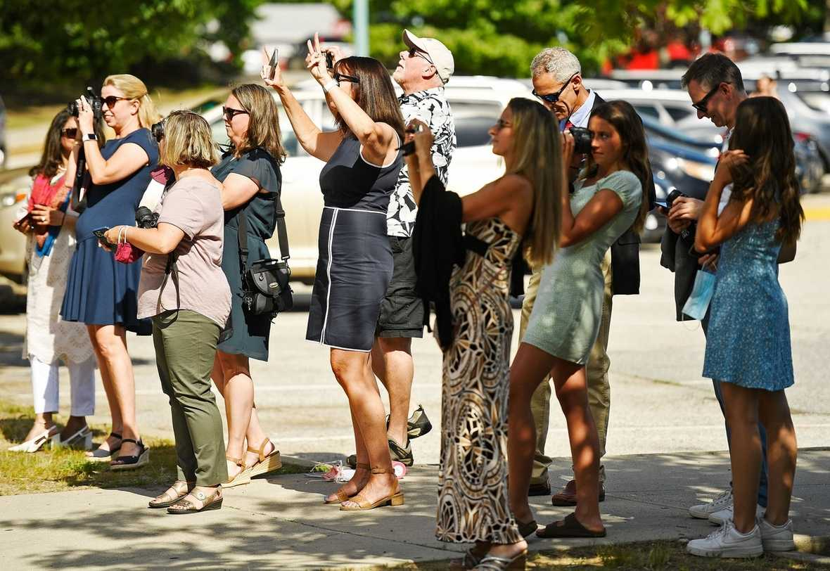 Family of members of the East Lyme High School Class of 2021 take photos of a group of graduates gathering for the 53rd commencement exercises at these school Wednesday, June 16, 2021. (Sean D. Elliot/The Day)