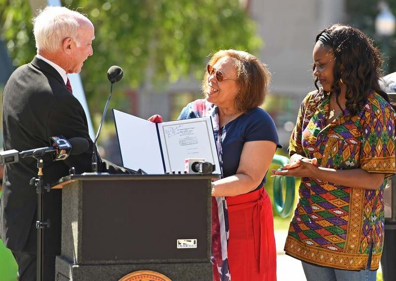 U.S. Rep. Joe Courtney, left, D-2nd District, presents Shiela Hayes, center, president of the Norwich Branch NAACP, and Lashawn Cunningham, chair of the Juneteenth Committee, with a copy of the bill making Juneteenth a federal holiday, autographed by sponsor Rep. Sheila Jackson Lee of Texas, during the Juneteenth celebration Friday, June 18, 2021, at City Hall Plaza in Norwich.  (Sean D. Elliot/The Day)