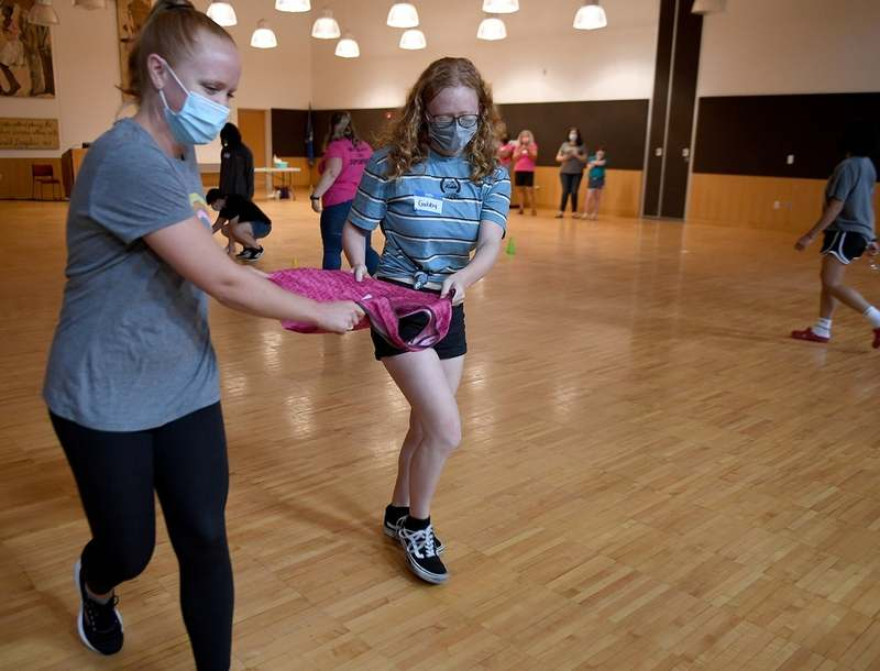 Instructor Alli Cyr, left, and Gabby Fedus, 16, of Montville, carry cotton balls in a bag as they participate in a relay race during S.T.E.P.S. Inc.'s summer program at Three Rivers Community College in Norwich on Monday, July 19, 2021. The four-week summer STEM enrichment program for teenage girls provides them an opportunity to learn about STEM career paths and socialize with peers from outside their high schools. (Sarah Gordon/The Day)