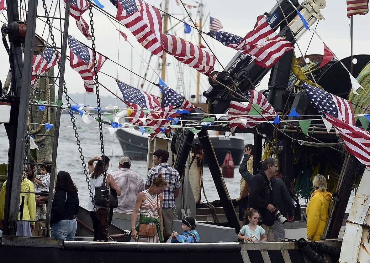 A small crowd gathers on the Tradition for the boat parade to lay a memorial wreath at sea during 67th annual Blessing of the Fleet at the Stonington Town Docks on Sunday, July 25, 2021. (Sarah Gordon/The Day)