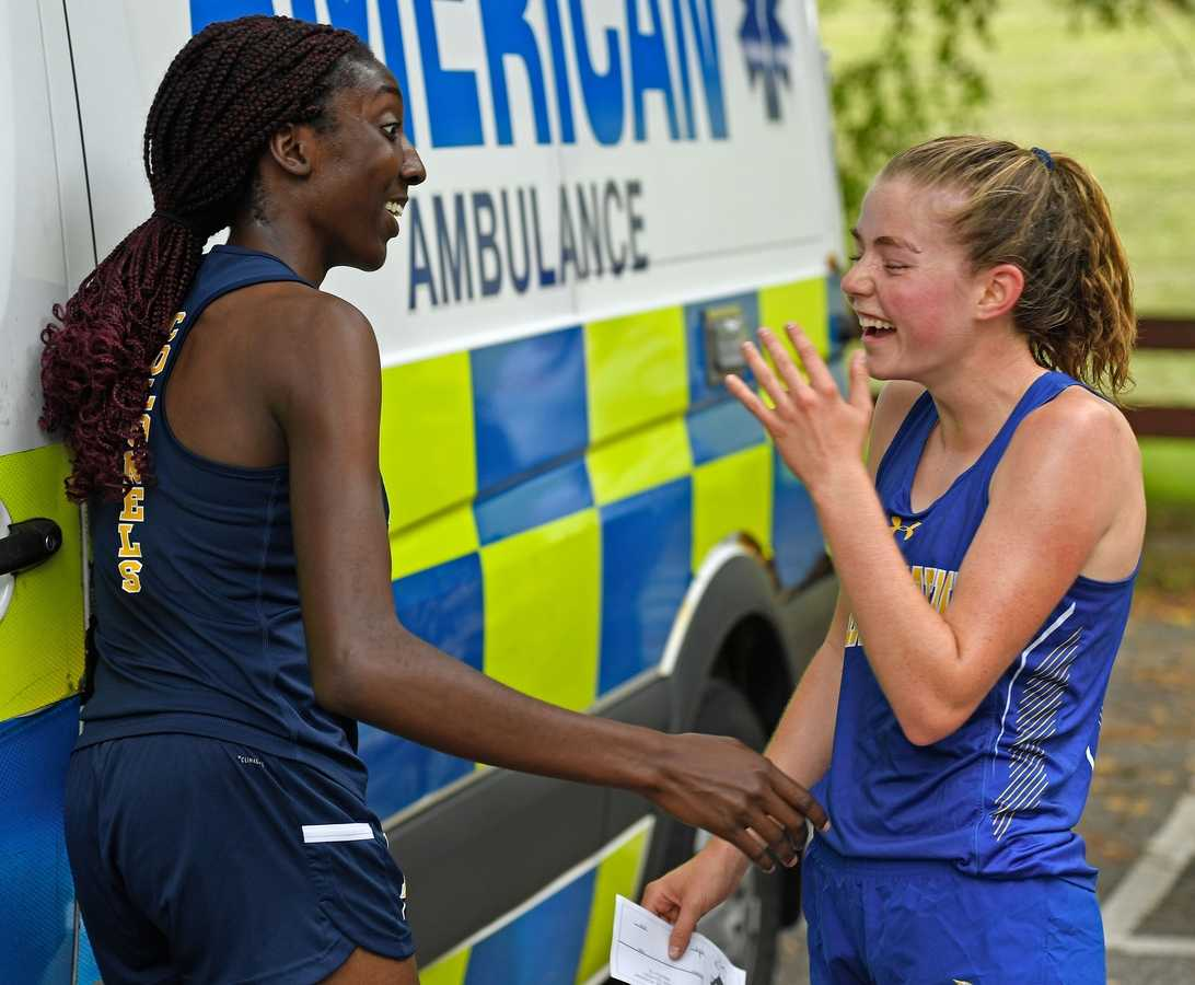Bacon Academy's Jordan Malloy, right, breaks into laughter after startling Ledyard runner Clare Inyang while attempting to congratulate her on a third place finish during a quad meet with NFA, Tourtelotte, Ledyard, and Bacon Academy Tuesday, September 14, 2021 at Mohegan Park in Norwich.   (Sean D. Elliot/The Day)